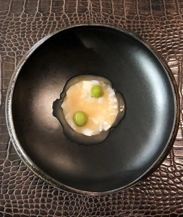 Tartar de calamar de alrededores con esférico de mojo verde hervido.
